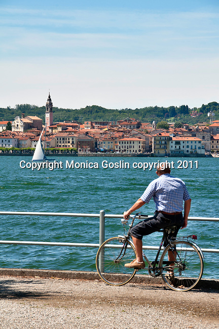 A man sits on his bike in the town of Angera, looking across Lake Maggiore, Italy at the town of Arona