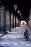 Old woman walking under the portales or colonnade, San Miguel de Allende, Mexico.