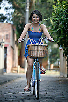 A young girl rides a beach cruiser in a city neighborhood.