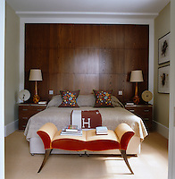 A pair of matching chest of drawers and lamps have been placed either side of the bed against the wood panelled wall of the bedroom