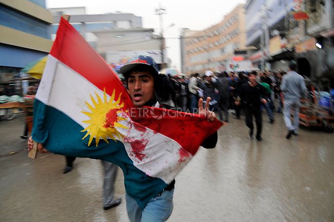 SULAIMANIYAH, IRAQ: A protester runs through the streets with a Kurdish flag stained with blood...Tension continues to grow in the semi-autonomous region of Iraqi Kurdistan as protesters clash with police on a 5th day of unrest...Photo by Akam Shekh Hadi