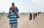 A Somali man who arrived in recent weeks at the Dadaab camp in northeastern Kenya carries his child as he walks to a new extension of the world's largest refugee settlement. Swelled with tens of thousands of recent arrivals fleeing drought in Somalia, the camp has been unable to absorb the newest arrivals. The Lutheran World Federation, a member of the ACT Alliance, is manager of the camp and in July began moving hundreds of families into tents in the extension.