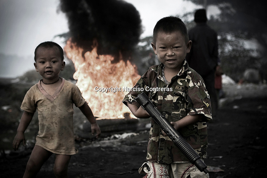 Refugee children whose fled from Karen state, Burma, play war at the rubbish dump of Mae Sot bordertown, Thailand.