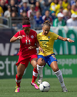 Canadian midfielder Desiree Scott (11) and Brazilian forward Thais (15) battle for ball at midfield. In an international friendly, Canada defeated Brasil, 2-1, at Gillette Stadium on March 24, 2012.