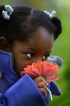 Shyann Montgomery smells a flower while playing in the garden at the Albina Early Headstart Richard Brown Center in Portland.