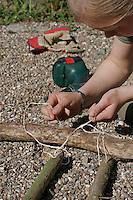 Kinder basteln Klangspiel aus Ästen, Mädchen verknotet Klanghölzer mit dem Rahmen-Ast