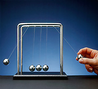 NEWTON TOY PENDULA: COLLISION EXPERIMENT<br /> Newton's Third Law Conservation of Momentum<br /> A double exposure - One pendulum bob used as a projectile collides with three other  bobs, causing an  displacement of one  bob equal to the original displacement of the projectile bob. The sum of momenta  of an isolated system is a constant.