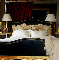In this bedroom of a London apartment a gilded bed has been upholstered in black leather and set against a dark red curtain