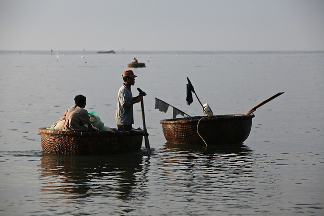 Fishermen work in traditional woven bamboo boats just off the beach in Mui Ne, Vietnam. Nov. 20, 2011.