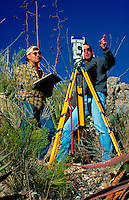 Surveyors discuss boundary locations during a ranch property survey using an Electronic Tachometer. Arizona.