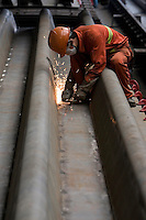 Worker grinding steel plates in a factory, Changxing Island, Shanghai, China