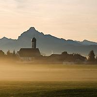 Wallfahrtskirche Maria Hilf  in the small village of Speiden with Early morning autumn mist and mountain peak Säuling in distance, Allgäu region, Bavaria, Germany