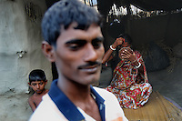 Nirmal Gayen, 27, at his home with wife Anjana and son Abhijit. Anjana dons vermillion (symbol of marriage for traditional Hindu women) after return of her husband from the forest. It has become a  custom due to fear among the forest goers wives that they cannot wear vermillion until their husbands come back. Sunderban, West Bangal, India. April 2011. Arindam Mukherjee