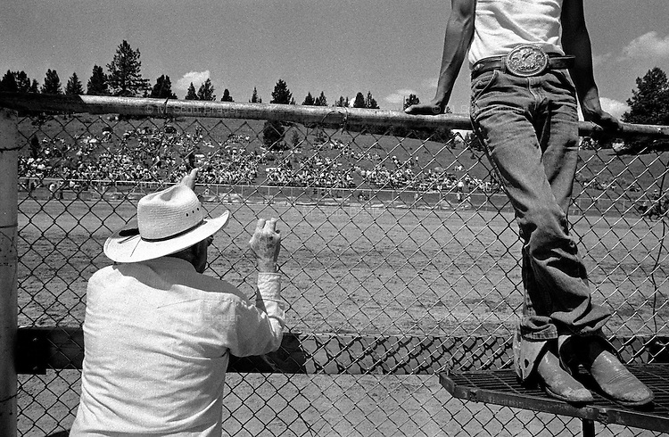 Spectators stand outside the fence at the annual Lincoln Rodeo in Lincoln, MT in June 2006.  The Lincoln Rodeo is an open rodeo, which means competitors need not be a member of a professional rodeo association.