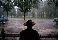 Summer rains come daily in the South. A man waits for the shower in a rocking chair on the front porch of a restaurant in a small town on the edge of the Okefenokee Swamp.