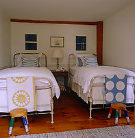 The boys' bedroom has a pair of wrought-iron framed beds with colourful quilts folded over the ends
