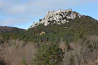 "Puilaurens Castle, Chateau de Puilaurens, Cathar castle, Lapradelle-Puilaurens, Boulzane Valley, Aude, France.  Also called Puylaurens, or lo Castel de Pueg-Laurenc in Occitan, this 12th century ruined castle had belonged to the Abbey of Saint-Michel de Cuxa before being acquired by the Queen of Aragon in 1162. It changed hands many times during the Albigensian Crusade. It is one of the ""Five Sons of Carcassonne"" or ""cinq fils de Carcassonne"" and is a listed monument historique. View from below showing forest and hilltop location. Picture by Manuel Cohen"