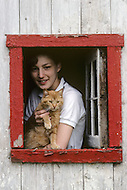 Ile D'Orleans, Quebec City Area, Canada, June 8, 1984. A girl with her cat inside an old farm.