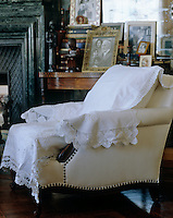 This upholstered white calico armchair is covered in an assortment of embroidered and lace-edged antique table linen