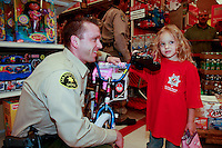 A San Diego Sheriff's Deputy helps a young girl choose between shoes at the Shop-With-a-Cop event at the Sports Arena Target store in San Diego on December 1, 2007.  Three hundred disadvantaged  children rose well before dawn in order to be ready for the fleet of buses that collected them from every corner of the county on Saturday morning.  The buses took them to SeaWorld where they were paired up with an officer for the the day.  After breakfast they made their way to the Target store in a huge, convoy of more than three hundred police vehicles with sirens blaring, lights flashing and Santa waving from a police helicopter hovering above them.  Each child had a $100 gift card to spend and many of them resisted the temptation to buy toys and choose instead to get clothes for themselves, their siblings or parents.