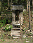 Wooden outhouse with steps in the forest in Colorado