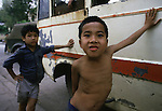 Tow boys lean on a bus in Hanoi, North Vietnam.  (Jim Bryant Photo).....