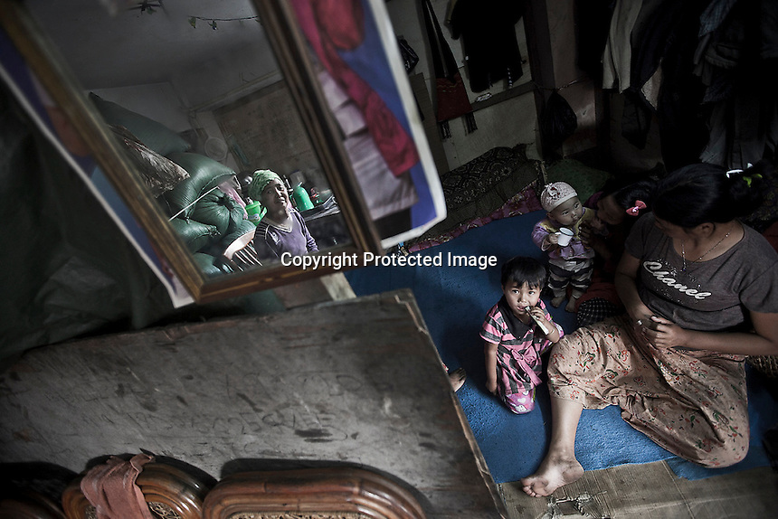 A Kachin refugee family settled in a basement of an abandoned compound in Laiza city. The compound gives shelter to two thousand displaced persons from the war-torn villages in Kachin State since the ceasefire was broken out by the Burmese army last June 2011. During months the fighting were spread out along the Kachin State leaving more than 40,000 displaced persons and refugees (a conservative estimating) in accord with the humanitarian aid groups.