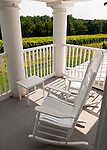 A pair of rocking chairs on the upstairs porch overlooks vineyards surrounding the manor house at General's Ridge Vineyard and Winery.