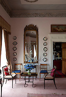One wall of the pale pink drawing room features a gilt-framed mirror flanked by displays of plates