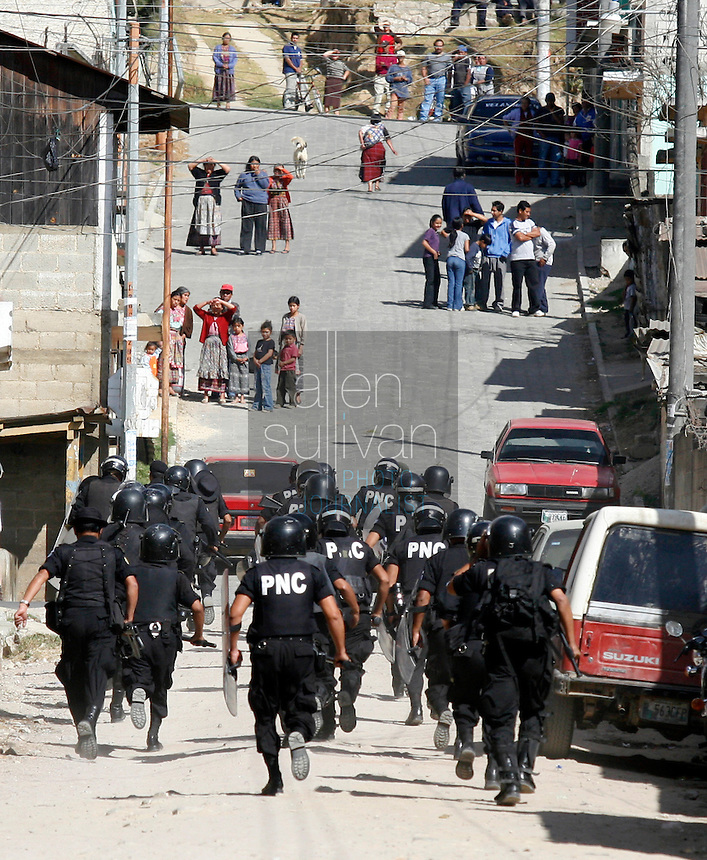 Police run to help others contain protests by indigenous people against U.S. President Bush in Tecpán Guatemala, Guatemala. Townspeople watch from afar on the street above. Bush visited a nearby Mayan site, Iximché.