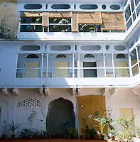 The top floor apartment shaded from the sun with rush blinds can be seen from the central courtyard