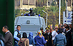 Egyptian policemen stand in front of an armored vehicle outside the Cairo University, one day after a court dismissed murder charges against former president Hosni Mubarak, Egypt, 30 November 2014. Two people were killed in clashes between police and demonstrators in Cairo after the court verdict. Nine people were wounded in the unrest that erupted near central Cairo's Tahrir Square, the epicenter of a 2011 uprising against Mubarak. Photo by Amr Sayed