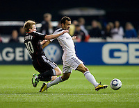 Dax McCarty (10) of D.C. United tries to tackle Juninho (19) of the LA Galaxy  during the game at RFK Stadium.  D.C. United tied the LA Galaxy, 1-1.