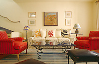 Scatter cushions with Matissean motifs are arranged on a sofa next to a contrasting pair of armchairs in grey-striped red upholstery