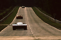 Three cars race away from the exit of Mulsanne Corner, late afternoon, during the 1985 24 Hours of Le Mans auto race.