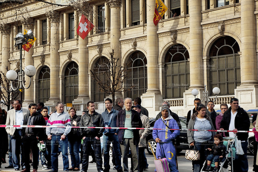 """Switzerland. Geneva. Paquis neighborhood. Police line, Do not cross. People watch rescuers and police officers dealing with the aftermath of a car accident. A swiss flag and two flags of Geneva on the building of the Mont-Blanc post office. The flag of Switzerland consists of a red flag with a white cross (a bold, equilateral cross) in the centre. It is a sovereign-state flag. The flag of Geneva is divided vertically into two equal parts, yellow (hoist) and red (fly). In the hoist, a black double-eagle with a red crown, beak, tongue, legs and claws, cut in half by the palar line. In the fly, a yellow upright key with its ward toward the fly. The eagle symbolises loftiness, justice and protection. The key symbolises ecclesiastical rule, treasuries, and responsibility. The arms of Geneva are actually two shields impaled: half the eagle of the Holy Roman Empire, and one of the two keys of St. Peter (the """"keys of heaven""""). 21.03.12 © 2012 Didier Ruef.."""