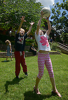 NWA Democrat-Gazette/BEN GOFF @NWABENGOFF<br /> Miller Rawn (left), 7, and London West, 10, both of Fayetteville, jump to catch the ball during a game of Newcomb ball on Sunday June 5, 2016 during a parish picnic after service at St. Paul's Episcopal Church in Fayetteville.