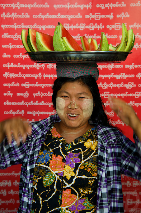 A women Vendor in front of a sign written in Burmese, that read Vendors and tricycle,Tuk-Tuk drivers are not allowed in this area. At Mandalay Railway Station, Myanmar/Burma