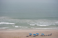 Morning on the beach with empty lounge chairs and surfers in the ocean at Mrtyle Beach, SC