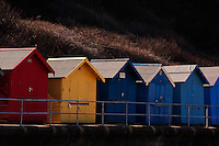 Primary colours of beach huts along the seashore at Cromer, Norfolk, England.
