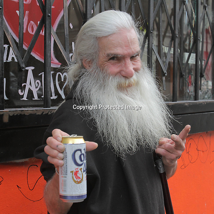 A man tries to share his beverage with the photographer in San Francisco Tenderloin district.