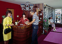 Tourist standing at hotel reception of the Fleur De Lis Motel