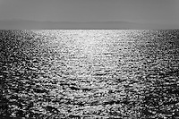 Shining, rippling water in black and white with faint mountain outline on the horizon.