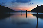 Old pilings silhoutted and reflected in the blue waters of Twilight on Wolf Lodge Bay, near Coeur D Alene, Idaho