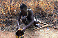 Yaeda Valley, Tanzania: Hoya, a Hadzabe man, tastes a comb of honey he has gathererd from a tree in this corner of Northern Tanzania. The Hadzabe are one of the last remaining tribes of hunter gatherers on Earth. For at least 60,000 years, or shortly after human evolution, they have survived on a diet of honey, roots, herbs and animals they slay with poison arrows, right.  (PHOTO: MIGUEL JUAREZ LUGO)