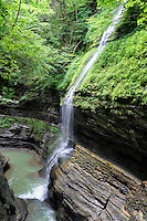 This image is looking down the gorge at one of the deeper parts of Watkins Glen State Park in New York, and is one of two interesting places to view this narrow falls of a tributary spilling in to the glen through the foliage. It is not only a waterfall, but a long-fall too.<br />