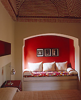 The bedroom has a niche where a comfortable daybed has been installed and is given dramatic effect with a bright red wall