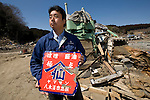 Michihiro Kohno, president and CEO of Yagisawa Shoten, stands by a press machine holding a company sign he has salvaged from the debris as he looks through the rubble that was once his 200-year-old soy sauce company's premises in Rikuzentakata, Iwate Prefecture Prefecture, Japan on 04 April 2011. Photograph: Robert Gilhooly