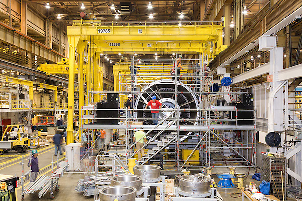 July 6, 2016. Greenville, South Carolina. <br />  Workers install scaffolding around a GE gas turbine. Scaffolding is integral to the assembly process as the massive turbine parts are moved by cranes around the plant and are lifted off the floor by large stands. <br />  At the General Electric Gas Turbine factory, engineers  design, produce, test and repair gas turbines for generating electricity. These turbines weigh more than 900,000 pounds and can create internal combustion temperatures up to 2,900 degrees F. Depending on the model, one of the GE turbines can produce enough electricity for half a million American households.