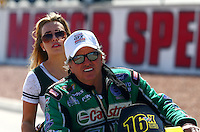 Mar 28, 2014; Las Vegas, NV, USA; NHRA funny car driver John Force gives his daughter top fuel driver Brittany Force a ride on his scooter during qualifying for the Summitracing.com Nationals at The Strip at Las Vegas Motor Speedway. Mandatory Credit: Mark J. Rebilas-